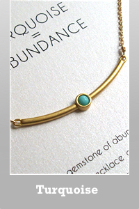 Dogeared curved bar inset with turquoise gem stone Abundance necklace.